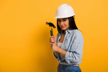 attractive female manual worker in helmet holding hammer on yellow