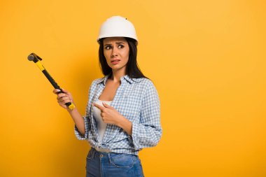 Frustrated workwoman in helmet holding hammer on yellow stock vector