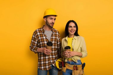 smiling manual workers holding coffee to go on yellow