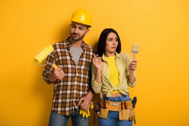 confused manual workers looking at paint roller and brush on yellow