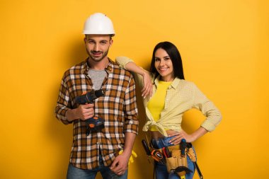 professional smiling manual workers with tool belt holding electric drill on yellow