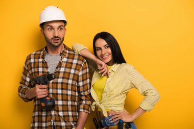 professional manual workers holding electric drill on yellow