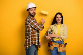 Photo smiling manual workers with paint roller and paint can on yellow