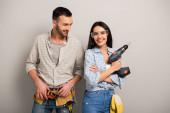 ochrana manuálních pracovníků držících elektrický vrták na šedé
