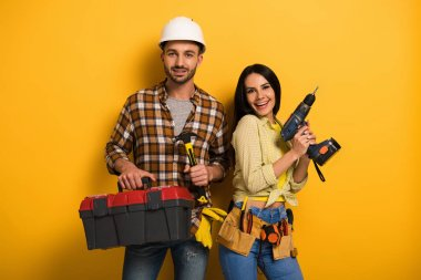 Smiling manual workers holding toolbox and electric drill on yellow stock vector