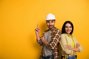happy manual workers pointing up on yellow