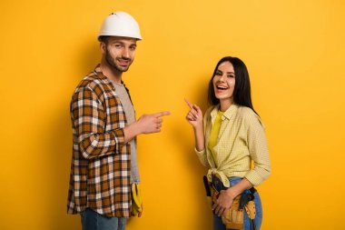 laughing manual workers pointing at each other on yellow