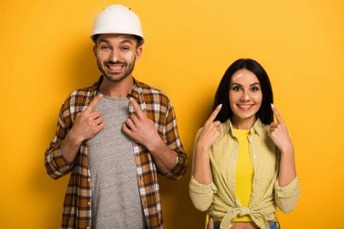 happy manual workers pointing at themselves on yellow