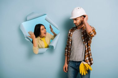 angry woman yelling at confused workman in helmet in torn paper, isolated on blue