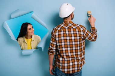 woman in torn paper looking at workman with paint brush, isolated on blue