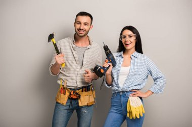 excited manual workers holding hammer and electric drill on grey