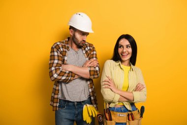smiling female manual worker and offended workman with crossed arms on yellow