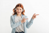 cheerful redhead teen girl listening music with headphones and pointing isolated on white