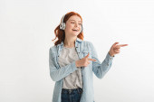 excited teen girl listening music with headphones and pointing isolated on white