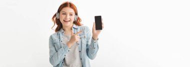 panoramic shot of happy teenager listening music with headphones and pointing at smartphone with blank screen, isolated on white
