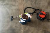 vrchní pohled na mladého uklízeče vysávání podlahy v kanceláři
