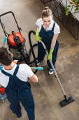 vysoký úhel pohledu na atraktivní čistič vysávání podlahy v blízkosti kolegy vozík s čisticími prostředky