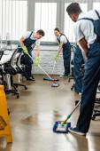 multikulturní tým mladých uklízečů mycích podlah s mopy v kanceláři