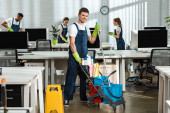 cheerful cleaner moving cart with cleaning supplies near multicultural colleagues