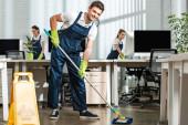 mladý čistič při pohledu na kameru při mytí podlahy s mop v moderní kanceláři