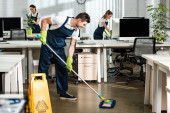 Photo young, smiling cleaner washing floor with mop in modern office