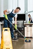 veselé čistič mytí podlahy s mop při úsměvu na kameru