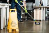 stříhaný z čistší mycí podlahy s mopem v blízkosti mokré podlahy varovné znamení