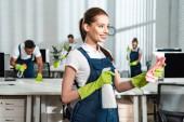 fröhliche, attraktive Reinigungskraft, die Spülmittel und Lappen in der Hand hält, während sie neben multikulturellen Kollegen steht