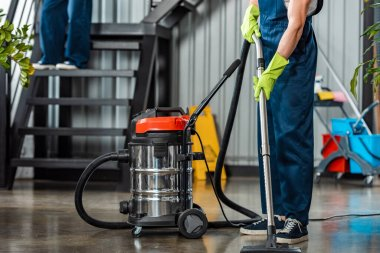 cropped view of cleaner in uniform cleaning floor with vacuum cleaner