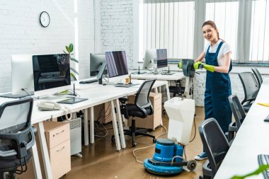 cheerful cleaner looking at camera while washing floor with cleaning machine