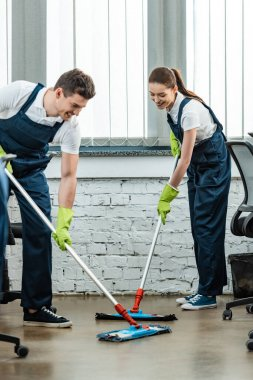two young cheerful cleaners in uniform washing floor with mops in office