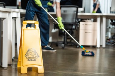 cropped of cleaner washing floor with mop near wet floor caution sign
