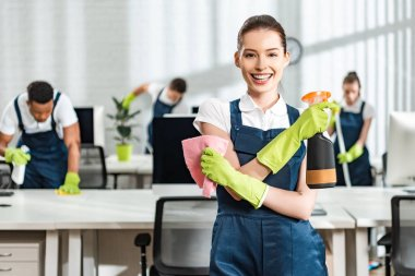 Happy cleaner with spray and rag smiling at camera while standing near multicultural colleagues stock vector