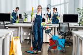 atraktivní čistič drží mop, zatímco stojí s rukou na boku v blízkosti multikulturní kolegové