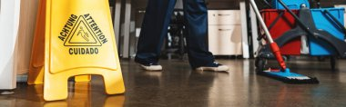 cropped view of cleaner washing floor with mop near wet floor caution sign, panoramic shot