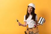 usmívající se údržbářka drží štětec a plechovku barvy na žlutém pozadí