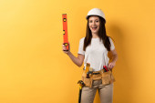smiling handywoman in helmet holding spirit level on yellow background