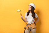 serious handywoman in helmet holding paint roller on yellow background