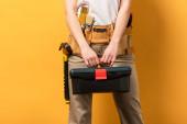 oříznutý pohled údržbářky držící nářadí na žlutém pozadí