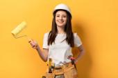 Fotografie Lächelnde Handarbeiterin mit Hand auf hüfthaltigem Farbroller auf gelbem Hintergrund