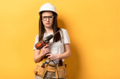serious handywoman holding drill and looking at camera on yellow background
