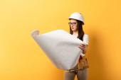 atraktivní údržbářka v helmě při pohledu na plán na žlutém pozadí