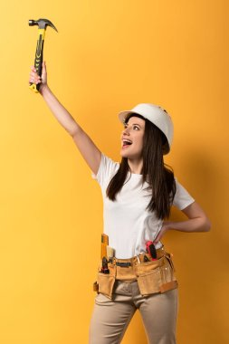 Happy handywoman holding hammer and screaming on yellow background stock vector