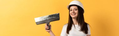 Panoramic shot of smiling handywoman holding trowel on yellow background stock vector