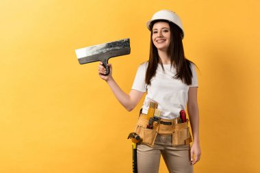 Smiling handywoman in helmet holding trowel on yellow background stock vector