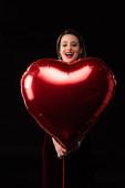 Fotografie šokovaná žena v šatech drží srdce ve tvaru balónu izolované na černé
