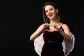 usmívající se žena v šatech s křídly ukazující srdce gesto izolované na černé