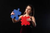 přemýšlivá žena v šatech drží puzzle postavy izolované na černé