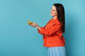 boční pohled na usmívající se žena drží papír motýl na modrém pozadí