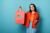 Photo smiling woman holding shopping bag with sex shop lettering on blue background